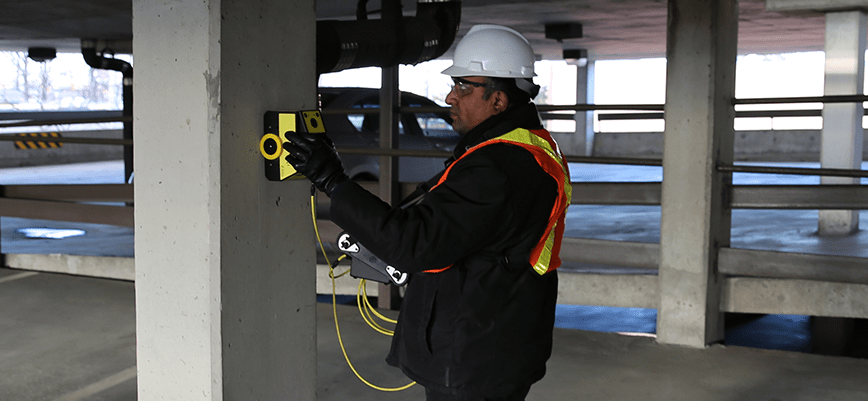 man scanning concrete pillar for rebar using gpr